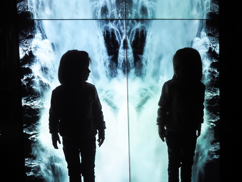 My daughter reflected in a mirror with a waterfall on a screen behind her at Swarovski Kristallwelten